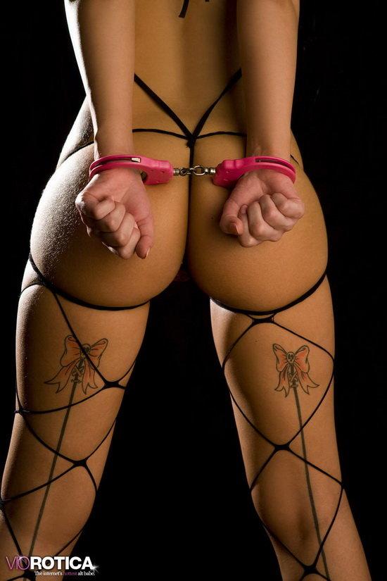 Эротические фотографии жгучей брюнеточки в садо-мазо костюме и наручниках