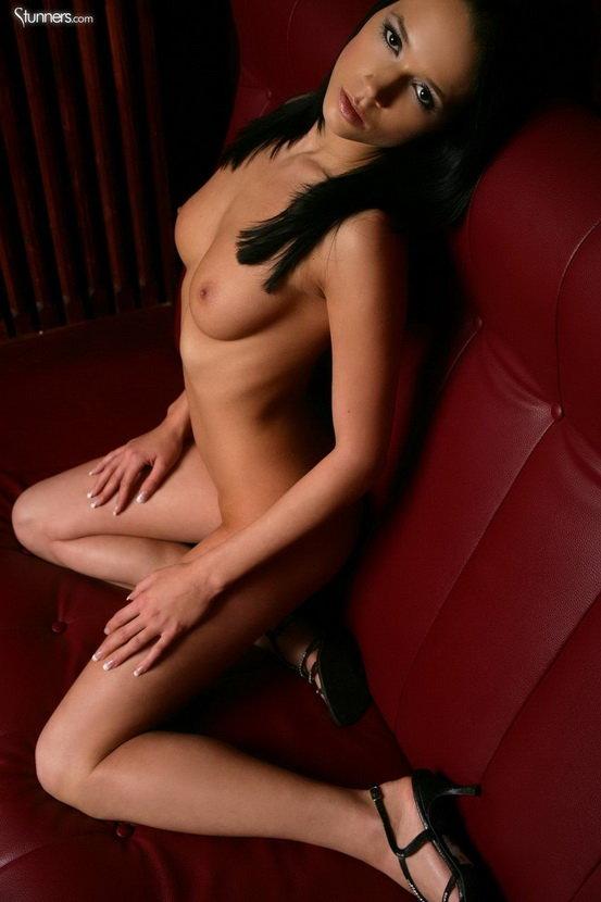 Эротические фотографии жгучей брюнетки на красных кожаных креслах
