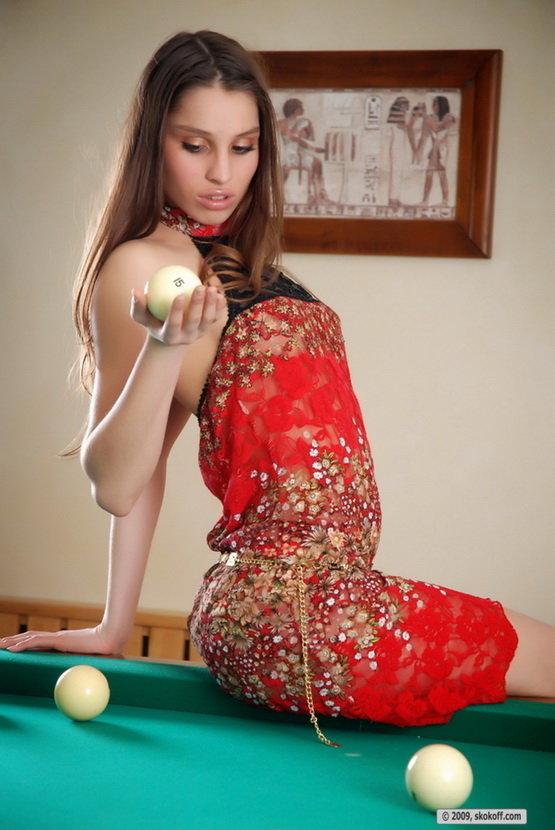 Эротические фотографии девушки в красном платье, играющей в бильярд