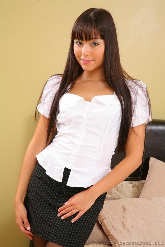 Эротические фотографии симпатичной черноволосой девушки в юбке, блузке и чёрных колготках.