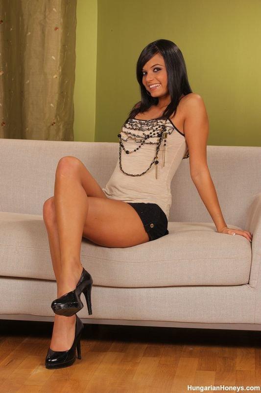 Эротическая фотогалерея улыбчивой девушки с черными волосами, позирующей на диванчике