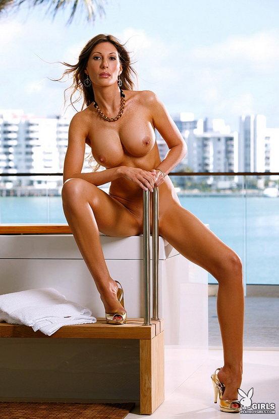 Красавица с большой грудью позирует на фоне моря