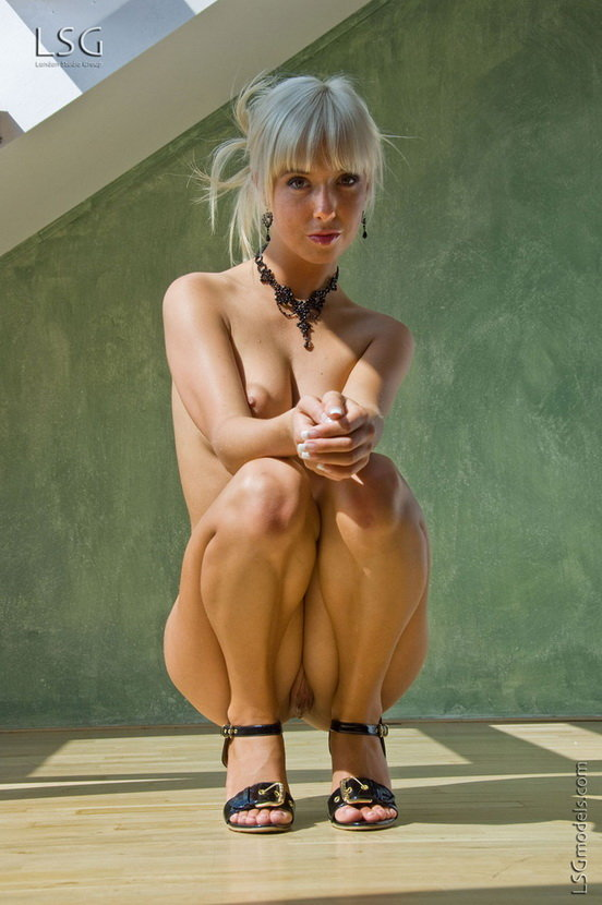 Необычная блондинка позирует на фоне окна