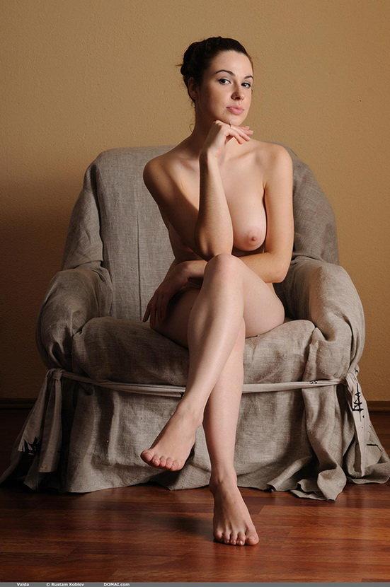 Милая девушка с красивой грудью позирует в кресле