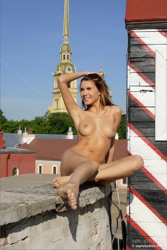 Эротические фотографии улыбчивой девушки на фоне полосатой будки