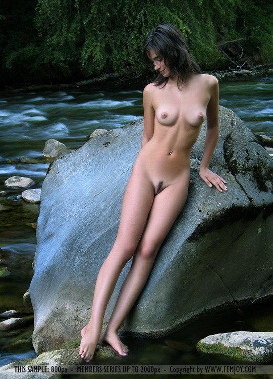 Молоденькая брюнетка позирует на камнях у реки