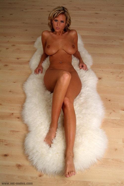 Девушка с большой грудью на белой овечей шкуре