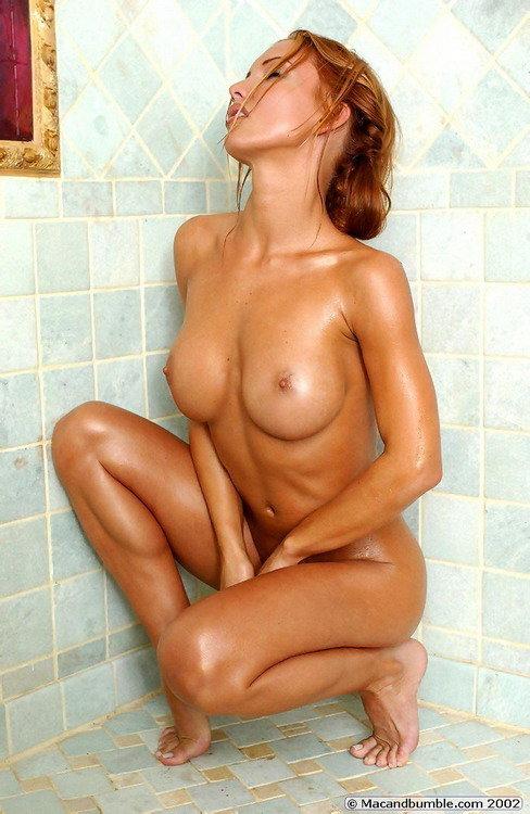 Рыжая девушка позирует в ванной комнате