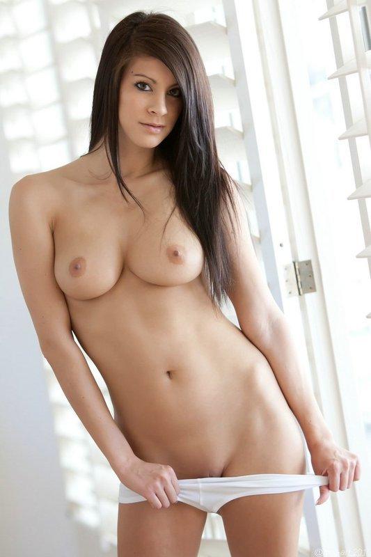 Девушка позирует на белом фоне - эротические фотографии