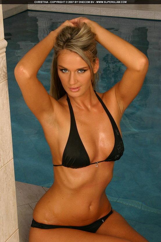 Девушка в черном купальнике позирует у бассейна