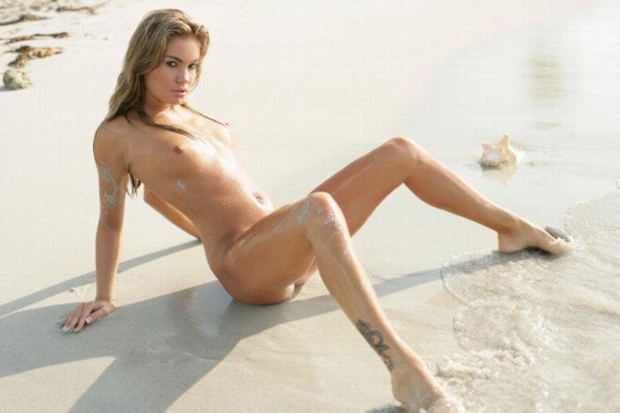 Эротическая фотосессия горячей шатенки в песке у прибоя