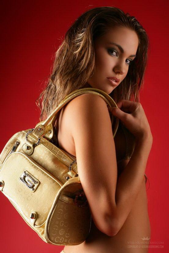 Эротическая фотосессия красивой девушки с сумочкой