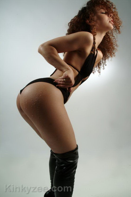 Эротическая фотосессия кудрявой девушки в высоких сапогах