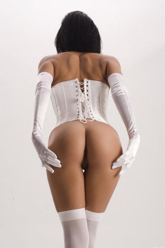 Эротическая фотосессия чувственной брюнетки в белом корсете