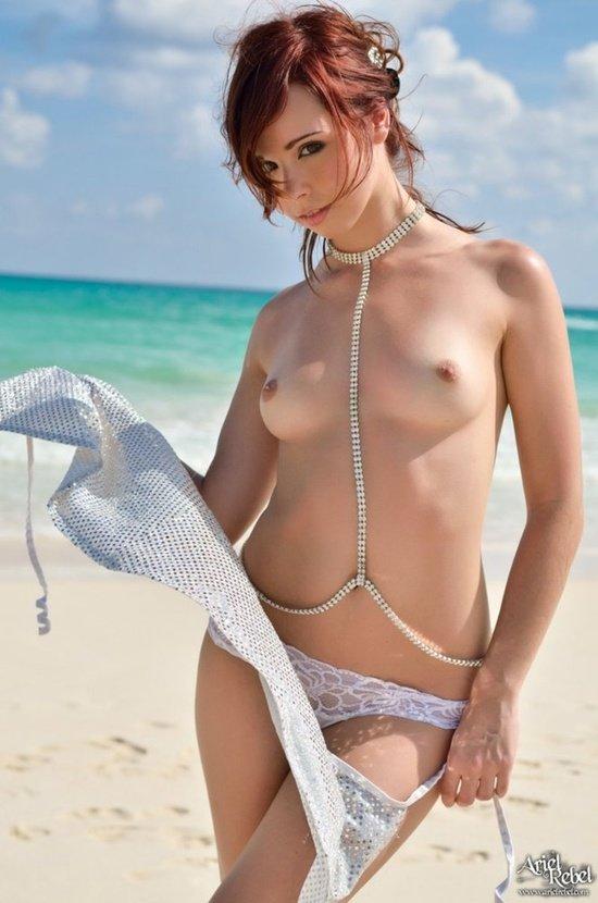 Эротическая фотосессия милой рыжеволосой девушки у моря