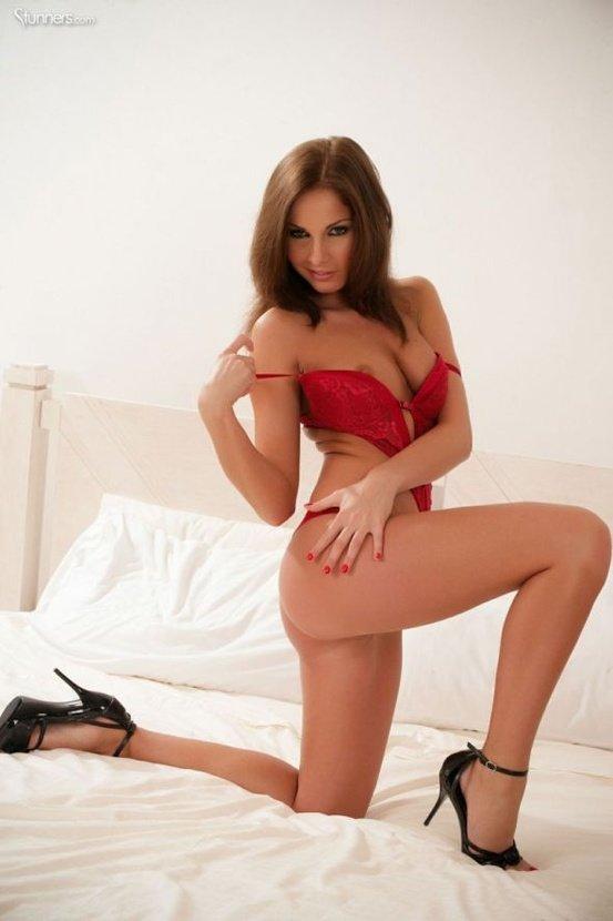 Эротическая фотосессия сексуальной шатенки в красном боди