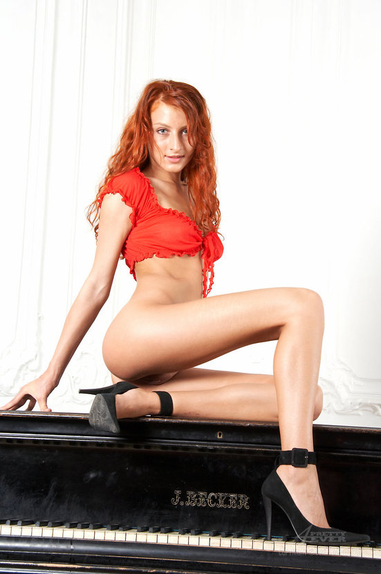 Эротические фото рыжеволосой девушки в красном костюме